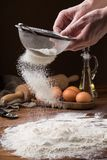 Sifting flour from a strainer on a wooden table Stock Photos