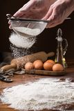 Sifting flour from a strainer on a wooden table Royalty Free Stock Images
