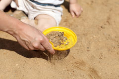 Sifting sand in sandbox. Mother is sifting sand in sandbox in summer Royalty Free Stock Photos