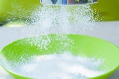 Sifting sugar powder in green bowl Stock Image
