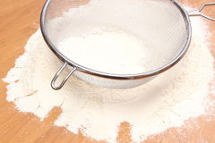 Sifting wheat flour through sieve Royalty Free Stock Image