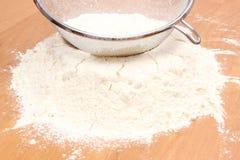 Sifting wheat flour through sieve Stock Image