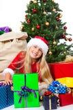 Sig.na Santa prima dell'albero di Natale e dei regali Fotografia Stock