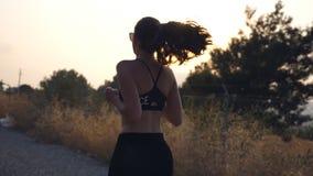 Siga à menina desportiva que movimenta-se na estrada secundária Jovem mulher nos óculos de sol que correm fora e música de escuta filme