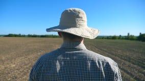 Siga al granjero de sexo masculino joven irreconocible en sombrero y camisa que camina en su campo en el día de verano soleado Ci almacen de video