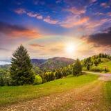 Siga el arco iris en alta tierra en la puesta del sol Foto de archivo libre de regalías