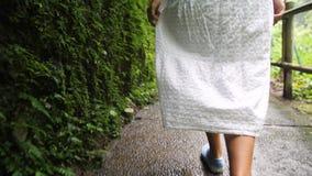 Siga el tiro de la chica joven en la selva que camina Forest Path y mirada del vestido blanco alrededor Viaje tranquilo y despreo almacen de metraje de vídeo