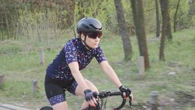 Siga el tiro del triathlete femenino en una bicicleta en el parque Vista lateral Concepto de entrenamiento del Triathlon C?mara l almacen de video