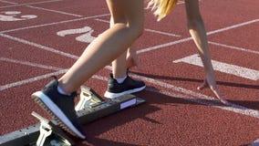 Siga a la mujer del corredor que se prepara para correr en los bloques el comenzar, entrenamiento activo, lento-MES almacen de video
