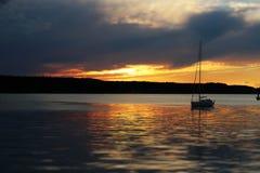 Siga la puesta del sol en el mar tranquilo con el velero fotografía de archivo libre de regalías