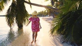 Siga-me conceito da jovem mulher que corre na praia ex?tica tropical Cadeira de plataforma na praia em Brigghton video estoque