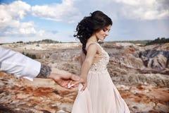 Siga-me Pares nas mãos da terra arrendada do amor A mulher conduz o homem Mo fotos de stock royalty free