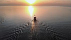 Siga o iate branco do navio - opini?o superior do farol do por do sol a?reo com os navios no fundo - paisagem morna do sol de aju filme