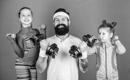 Siga o pai Crian?as bonitos das meninas que exercitam com pesos com paizinho Conceito do exemplo da motiva??o e do esporte Repeti imagem de stock