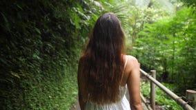 Siga o tiro da moça na selva de passeio Forest Path e vista do vestido branco ao redor Curso calmo e despreocupado 4K do estilo d filme