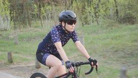 Siga o tiro do triathlete fêmea em uma bicicleta no parque Vista lateral Conceito de formação do Triathlon vídeos de arquivo