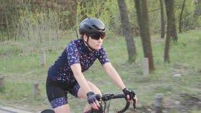 Siga o tiro do triathlete f?mea em uma bicicleta no parque Vista lateral Conceito de forma??o do Triathlon Movimento lento video estoque