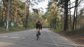 Siga para trás o tiro do ciclista que corre fora da sela Treinamento do ciclismo Conceito do ciclismo Movimento lento video estoque