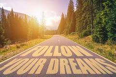 Siga su texto de los sueños escrito en el camino en las montañas imágenes de archivo libres de regalías
