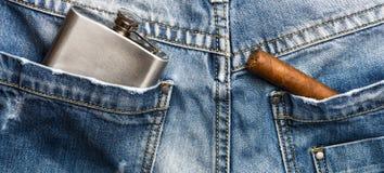 Sigaar en alcoholdrank in achterzak van broek Elitealcohol en sigaar Gastronomisch concept Gewoonte om elitetabak te roken stock foto