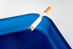 Sigaret en blauwe ashtry Stock Foto's