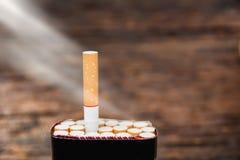 Sigaret en sigaretdoos met zonstraal op houten stock foto's