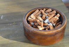 Sigaretfilter in ceramisch asbakje stock foto's