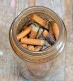 Sigaretfilter in glasfles stock foto's