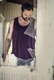 Sigaretta del fumo dell'uomo dietro la finestra rotta Fotografia Stock Libera da Diritti