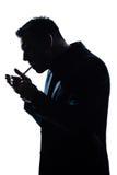 Sigaretta di fumo di illuminazione del ritratto dell'uomo della siluetta Fotografia Stock Libera da Diritti