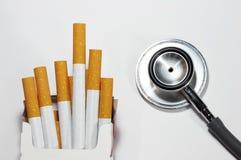Sigaretta e stetoscopio isolati su bianco Fotografia Stock Libera da Diritti