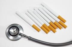 Sigaretta e stetoscopio isolati su bianco Fotografie Stock Libere da Diritti