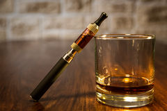 Sigaretta elettronica e un vetro di whiskey Immagine Stock