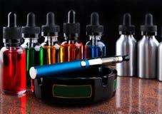Sigaretta elettronica sul portacenere e sulle bottiglie con il liquido del vape su fondo nero Fotografia Stock