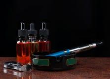 Sigaretta elettronica sul portacenere, sull'accendino e sulle bottiglie con il liquido del vape su fondo nero Immagine Stock