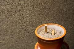 Sigarette affumicate in portacenere sulla notte Immagine Stock