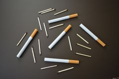 Sigarette con le partite su un fondo opaco marrone fotografia stock libera da diritti