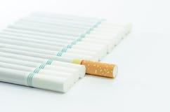 Sigarette con un macro colpo del filtro marrone nel fondo bianco Fotografie Stock