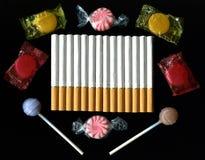 Sigarette e Candy su fondo nero Fotografia Stock Libera da Diritti