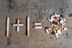Sigarette e pillole su una superficie di legno Fotografia Stock Libera da Diritti