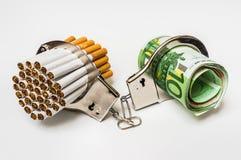 Sigarette e soldi con le manette - costo di fumo Fotografia Stock
