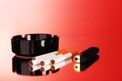 Sigarette, portacenere ed accenditore su priorità bassa rossa Fotografie Stock