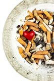Sigarette in un portacenere di vetro su un fondo bianco Trattamento del cancro polmonare Industria del tabacco Fotografie Stock Libere da Diritti