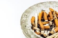 Sigarette in un portacenere di vetro su un fondo bianco Trattamento del cancro polmonare Industria del tabacco Immagine Stock