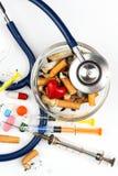 Sigarette in un portacenere di vetro su un fondo bianco Trattamento del cancro polmonare Stetoscopio e farmaco Immagine Stock