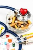 Sigarette in un portacenere di vetro su un fondo bianco Trattamento del cancro polmonare Stetoscopio e farmaco Immagini Stock Libere da Diritti