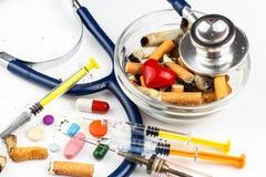 Sigarette in un portacenere di vetro su un fondo bianco Trattamento del cancro polmonare Stetoscopio e farmaco Fotografia Stock Libera da Diritti