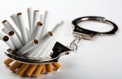 Sigaretten die aan handcuffs worden gesloten stock afbeelding