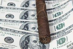 Sigaro cubano sui dollari Fotografia Stock