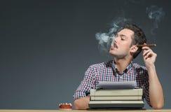 Sigaro di fumo dell'autore alla macchina da scrivere Immagine Stock
